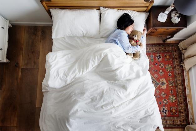 Asiatin, die mit einer puppe schläft