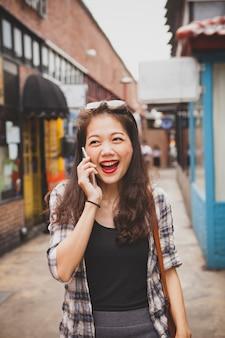 Asiatin, die mit glückgefühl im modernen einkaufsviertel lacht