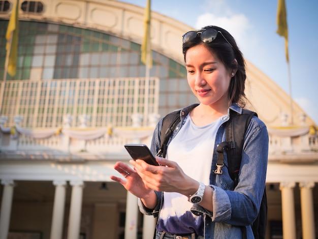 Asiatin, die mit handy reist