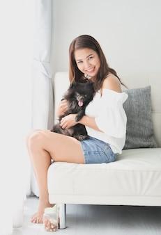Asiatin, die mit kleiner hundeschwarzfarbe im wohnzimmerlebensstilmädchen mit haustier spielt