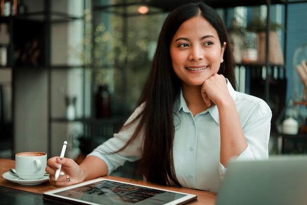 Asiatin, die mit laptop-computer im kaffeestubecafé arbeitet