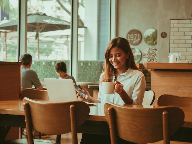 Asiatin, die mit laptop im kaffeeshopcafé arbeitet