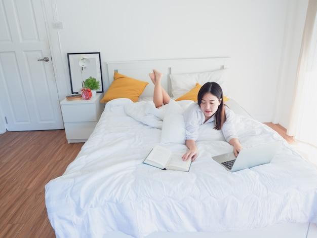 Asiatin, die morgens computer und gelesenes buch auf bett verwendet