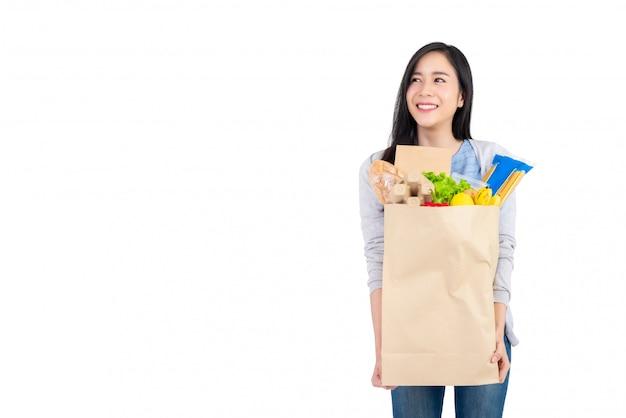 Asiatin, die papiereinkaufstasche voll vom gemüse und von den lebensmittelgeschäften hält