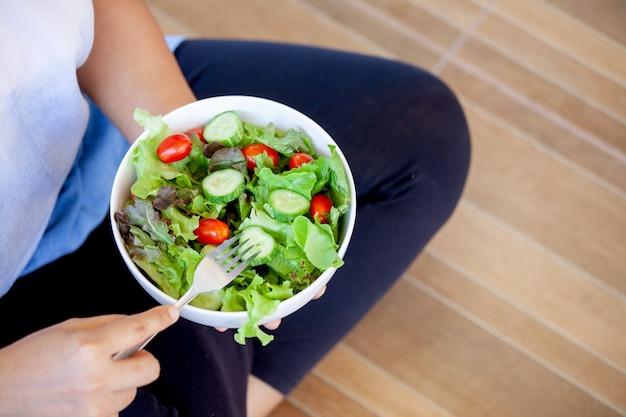 Asiatin, die salatschüssel hält und gesundes gemüse isst