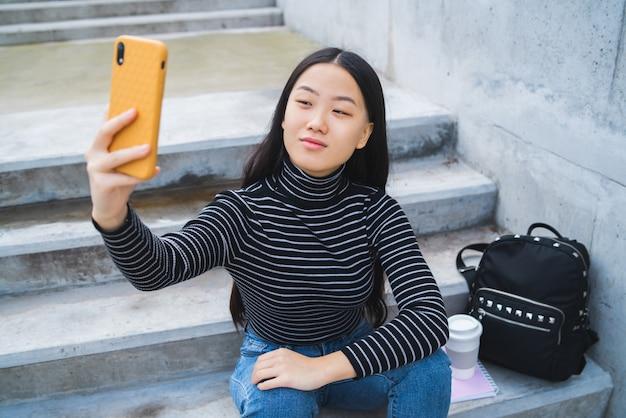 Asiatin, die selfie mit telefon nimmt.