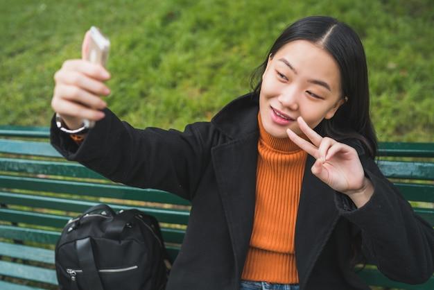 Asiatin, die selfie mit telefon nimmt