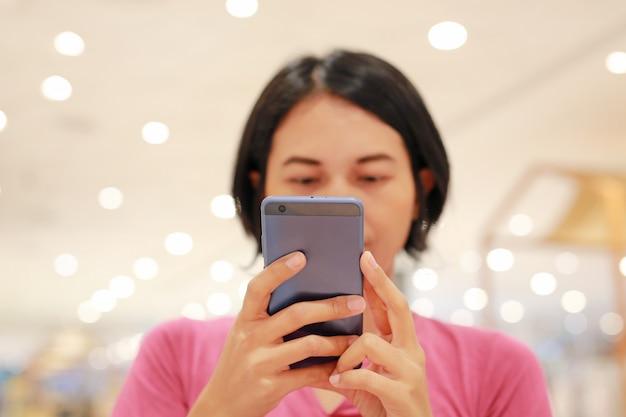 Asiatin, die smartphone auf tabelle am kaufhaus verwendet.