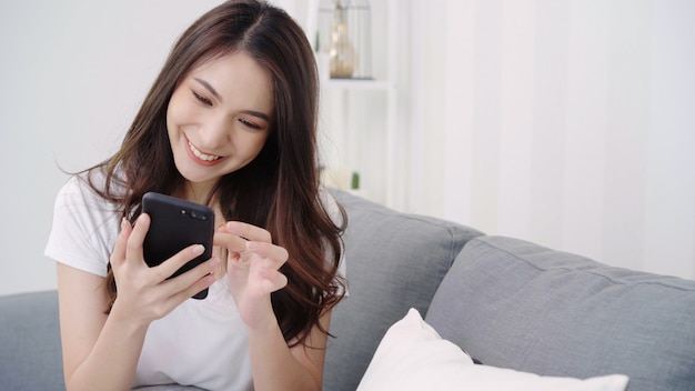Asiatin, die smartphone beim lügen auf hauptsofa in ihrem wohnzimmer spielt.