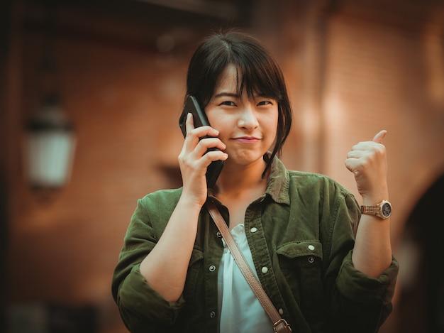Asiatin, die smartphone mit glücklicher stimmung im einkaufszentrum verwendet