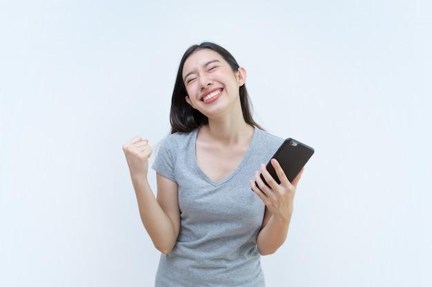Asiatin, die smartphone, schöne junge frau froh hält, um sieg zu erreichen