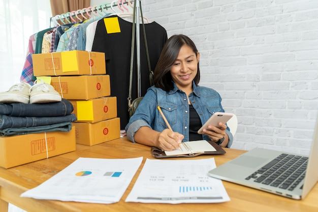 Asiatin, die smartphone verwendet, das online-start-up-kleinunternehmer verkauft