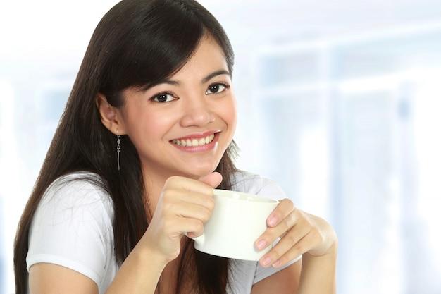 Asiatin, die tee trinkt
