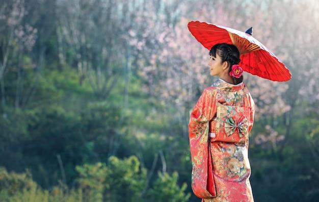 Asiatin, die traditionellen japanischen kimono, kirschblüte-hintergrund trägt