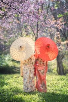 Asiatin, die traditionellen japanischen kimono mit rosa blume trägt