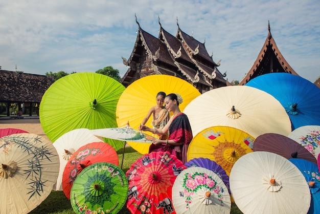 Asiatin, die traditionellen kostümmalereiregenschirm, lanna-art nord-chiangmai thailand trägt