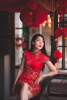 Asiatin, die traditionelles rotes kleid cheongsam stationiert auf der stuhl-mode-posting-stange trägt