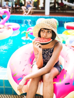 Asiatin, die tropisches sommerfest der wassermelone auf dem pool isst