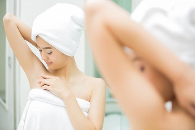 Asiatin, die unter der achselhöhle in der dusche schaut