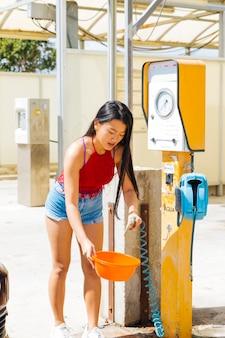 Asiatin, die wasser in der schüssel an der tankstelle erhält