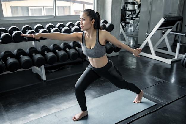 Asiatin, die yoga in der turnhalle spielt.