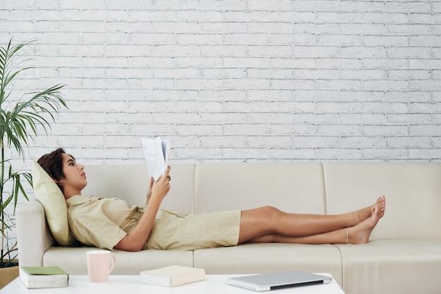 Asiatin, die zu hause auf couch und lesebuch liegt