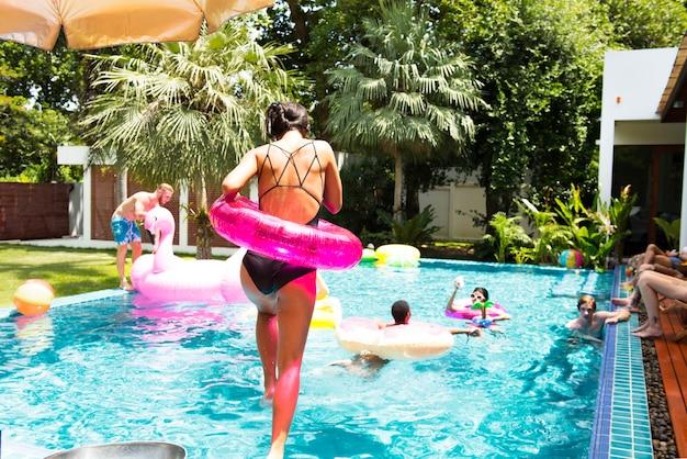 Asiatin, die zum pool mit aufblasbarem rohr springt