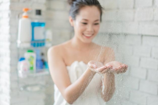 Asiatin duscht im badezimmer