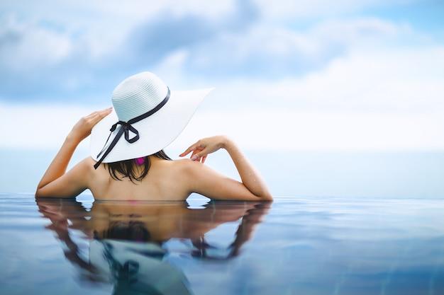 Asiatin entspannen sich im pool auf strand
