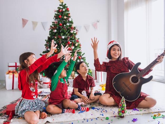 Asiatin feiert weihnachten, indem sie die gitarre zum kind strebt, kinder spielen zusammen am weihnachtstag mit weihnachtsbaum