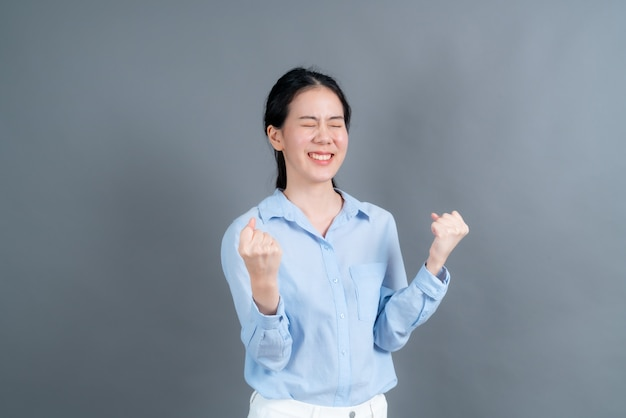 Asiatin freut sich über ihren erfolg und sieg und ballt vor freude die fäuste.