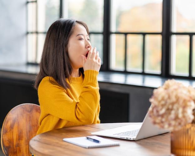 Asiatin gähnt wegen überarbeitung und erschöpfung. junge dame im leuchtend gelben pullover