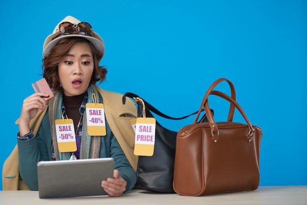 Asiatin, gekleidet in der neuen kleidung mit den rabattaufklebern, sitzend mit tablette und kreditkarte