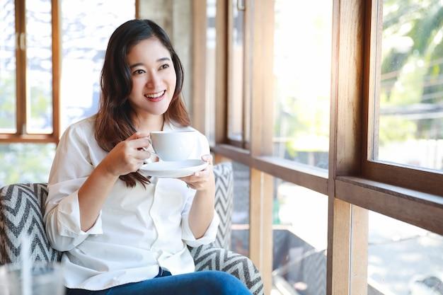 Asiatin genießen mit der kaffeetasse, die außerhalb der kaffeestube schaut