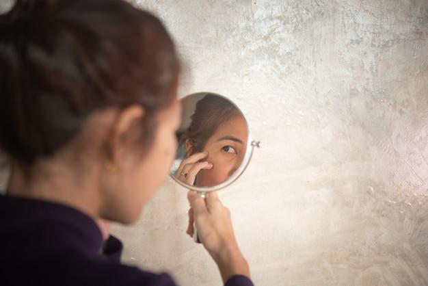 Asiatin glänzt im spiegel, um falten und graues haar zu sehen.