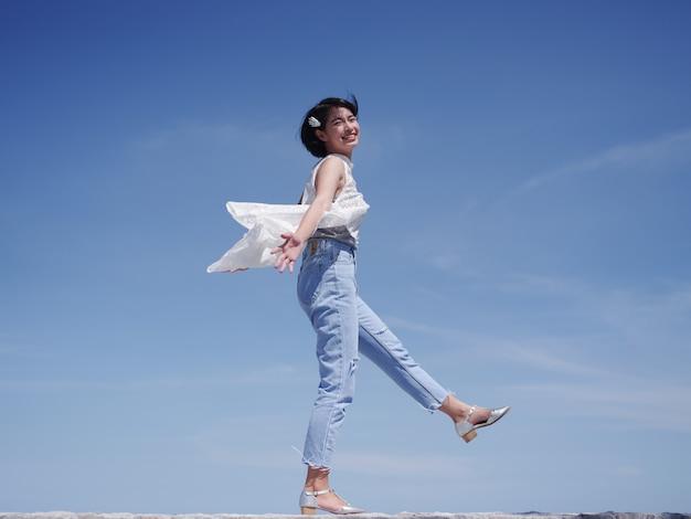 Asiatin glücklich und lächeln auf dem strand und dem blauen himmel