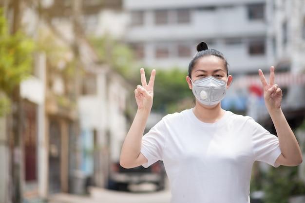 Asiatin hebt zwei hände, um einen symbolsieg zu erringen, indem sie eine maske trägt, um pm 2.5 staub und koronavirus zu verhindern, covid 19