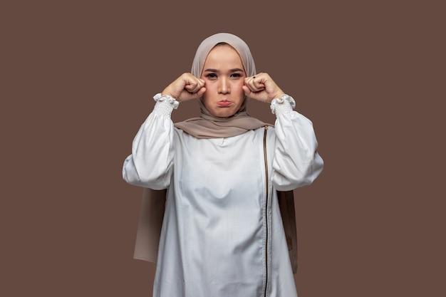 Asiatin hijab posiert weinend und trauriger ausdruck isoliert auf einfarbigem hintergrund