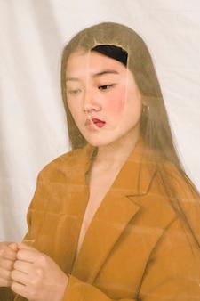 Asiatin hinter transparentem gewebe