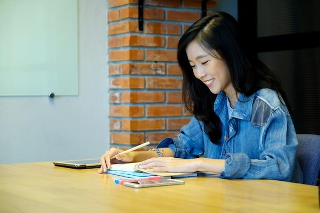 Asiatin-hochschulstudent im zufälligen schreiben auf papiernotizbuch,