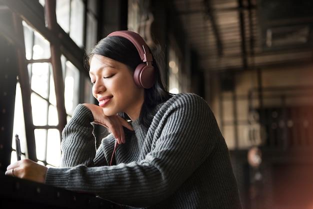 Asiatin-hörendes musik-kopfhörer-schreibens-notizbuch-konzept