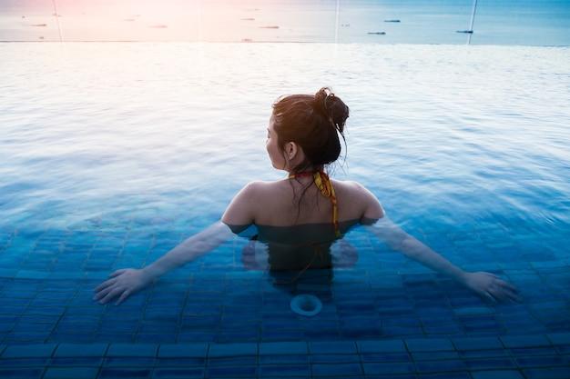 Asiatin im bikini, der am pool-sommercompept sich entspannt
