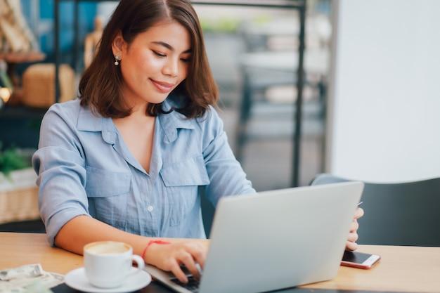 Asiatin im blauen hemd in trinkendem kaffee des cafés und in der anwendung des online-marketings des laptop-computer arbeitsgeschäfts