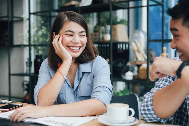 Asiatin im blauen hemd in trinkendem kaffee des cafés und in der unterhaltung mit freundlächeln und glücklichem gesicht