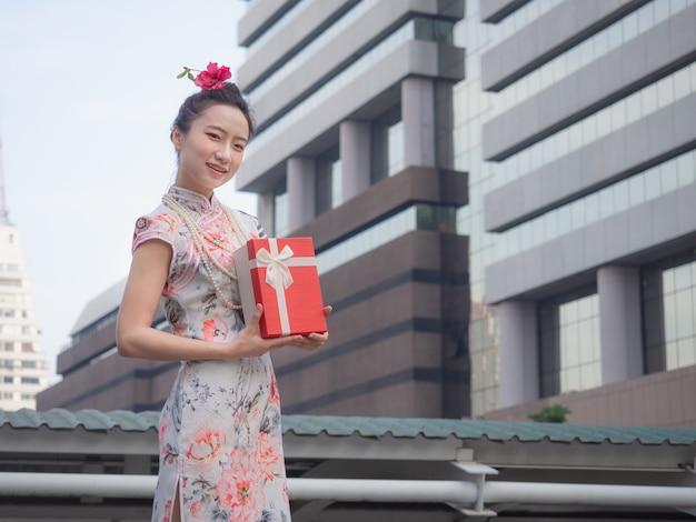 Asiatin im chinesekleid, das in der hand rote geschenkbox mit stadthintergrund hält