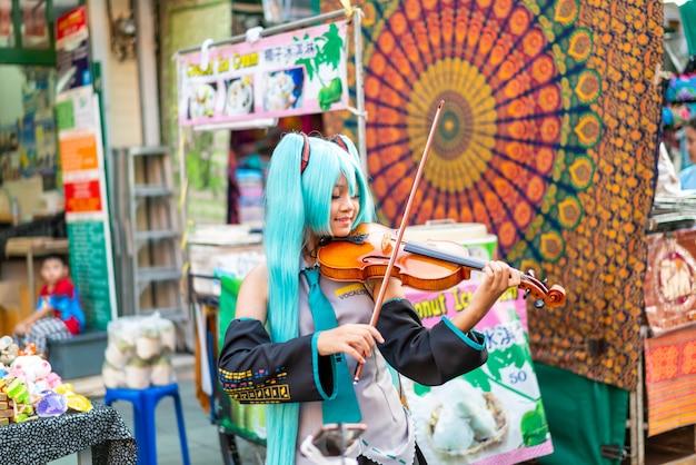 Asiatin im cosplay-kostüm, das geige an der khao sarn road spielt