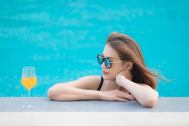 Asiatin im pool mit glas orangensaft