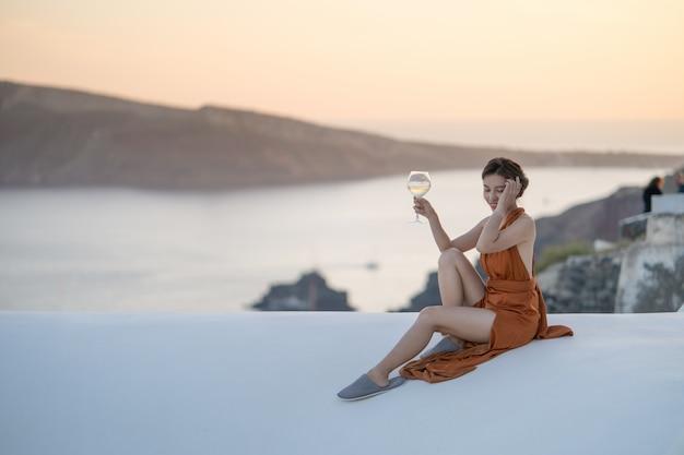 Asiatin im sexy kleid mit einem glas wein dorf ansicht oia in santorini-insel, griechenland genießend.