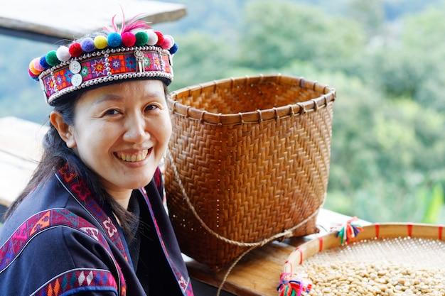 Asiatin im stammkleid ist das lächeln, das mit kaffeesamen glücklich ist