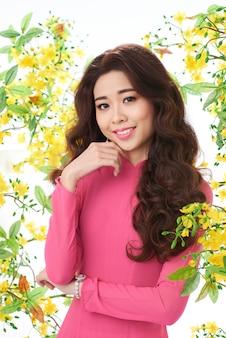 Asiatin im trachtenkleid, das im blühenden garten steht